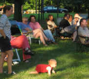 Concert-goers watching a baby crawl toward the action