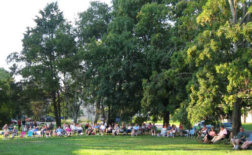 100 West End concert-goers enjoy the late afternoon sun under towering trees on the Seminary lawn